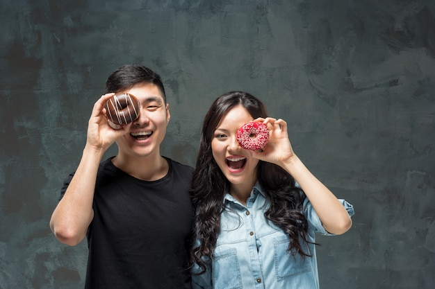 Het jonge aziatische paar geniet van etend van zoete kleurrijke doughnut Gratis Foto