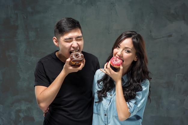 Het jonge aziatische paar geniet van het eten van zoete kleurrijke doughnut Gratis Foto