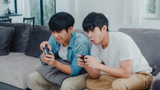 Het jonge aziatische vrolijke paar speelt thuis spelen, tien koreaanse lgbtq-mannen die joystick gebruiken die grappig gelukkig ogenblik samen op bank in woonkamer hebben bij huis. Gratis Foto