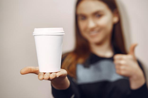 Het jonge baristameisje maakt koffie en glimlacht Gratis Foto