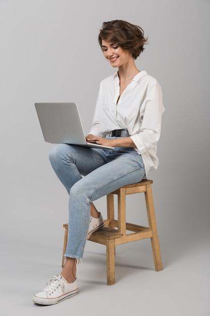 Het jonge bedrijfsvrouw stellen geïsoleerd over grijze muurzitting op kruk die laptop computer met behulp van Premium Foto