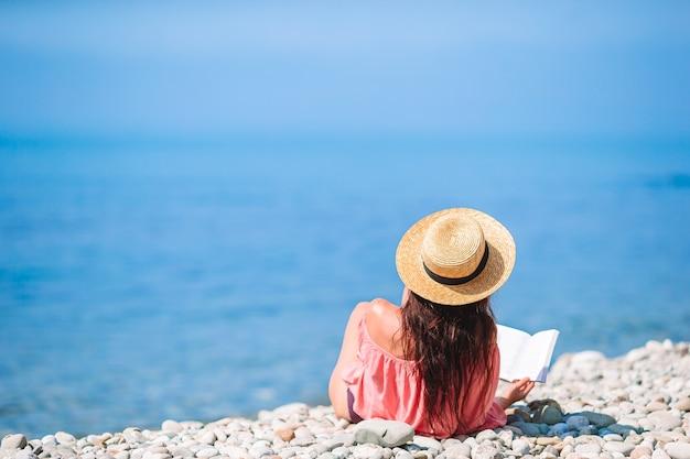 Het jonge boek van de vrouwenlezing tijdens tropisch wit strand Premium Foto