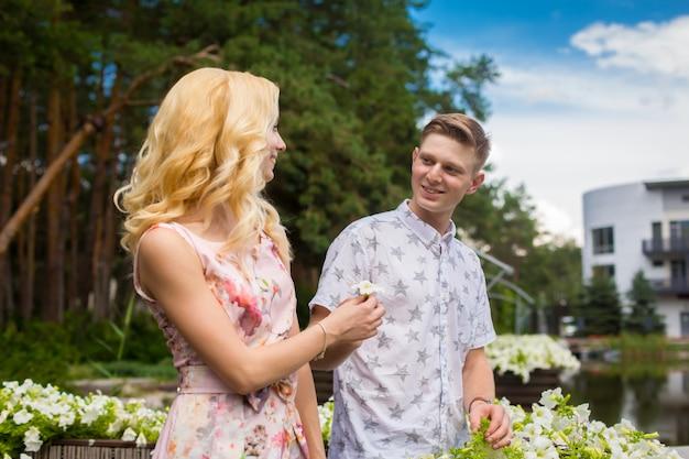 Het jonge charmante blondemeisje flirt en met een kerel in de tuin Premium Foto