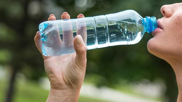 Het jonge close-up van het vrouwen drinkwater Gratis Foto