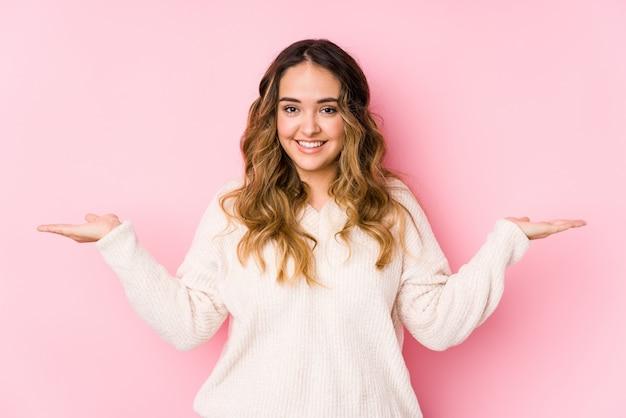 Het jonge curvy vrouw stellen in een roze geïsoleerde muur maakt schaal met wapens, voelt gelukkig en zeker. Premium Foto