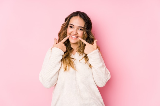 Het jonge curvy vrouw stellen in een roze muur isoleerde glimlachen, die vingers richten op mond. Premium Foto