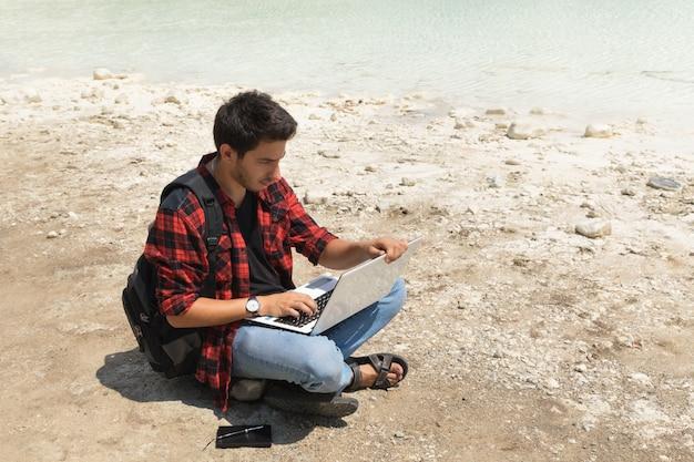 Het jonge donkerbruine mannetje in jeans en overhemd werkt bij een computer terwijl het zijn aan de aard. Premium Foto