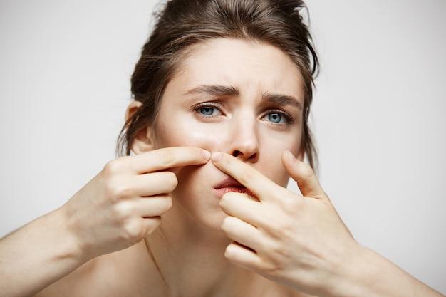 Het jonge donkerbruine meisje ontevreden van haar gezichtshuid van de probleemacne over witte achtergrond. gezondheidskosmetiek en huidverzorging. Gratis Foto
