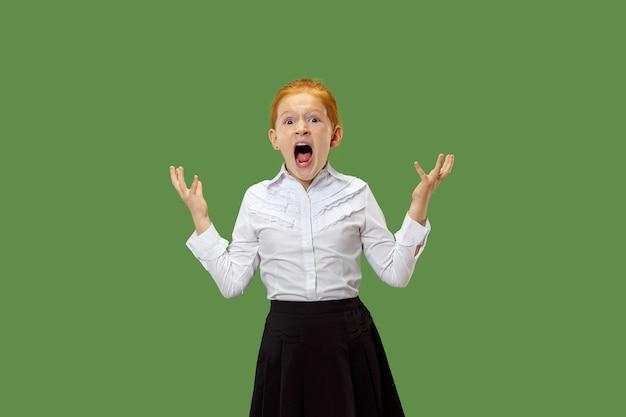 Het jonge emotionele boze tienermeisje dat op groene studioachtergrond gilt Gratis Foto