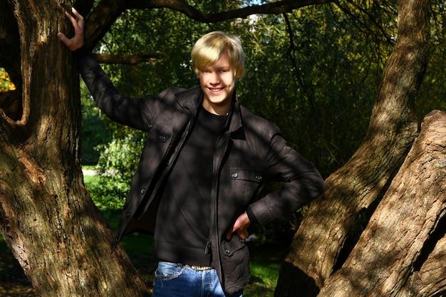 Het jonge en aantrekkelijke kerel stellen in park Gratis Foto