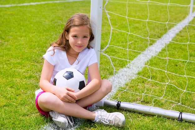 Het jonge geitjemeisje van de voetbal dat op gras met bal wordt ontspannen Premium Foto