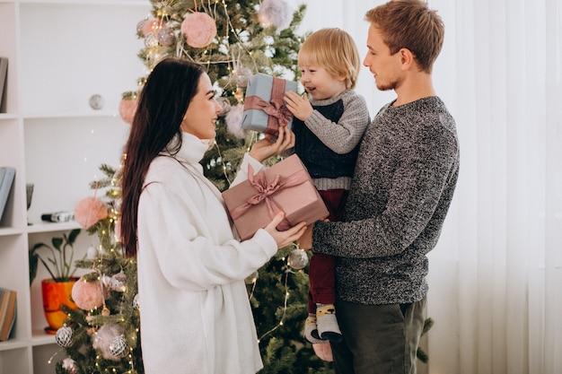 Het jonge gezin met zoontje door kerstboom met kerstcadeautjes Gratis Foto