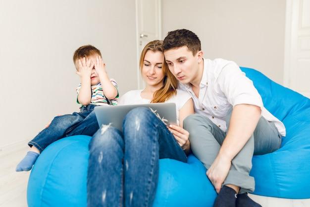 Het jonge gezin van twee ouders en één jongenskind zit op blauwe zakstoelen. Gratis Foto