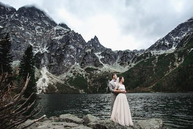 Het jonge huwelijkspaar stellen op de kust van het meer morskie oko, polen, tatra Premium Foto