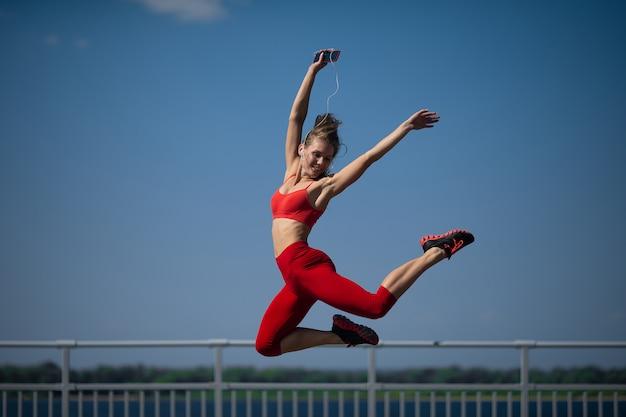 Het jonge kaukasische meisje voert streng uit die op hemel backround springen. Premium Foto
