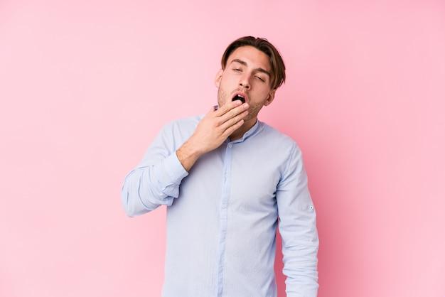 Het jonge kaukasische mens stellen in een roze muur isoleerde geeuw tonend een vermoeid gebaar die mond behandelen met hand. Premium Foto