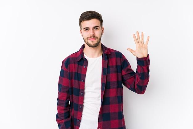 Het jonge kaukasische mens stellen in een witte muur isoleerde het glimlachen vrolijk tonend nummer vijf met vingers. Premium Foto