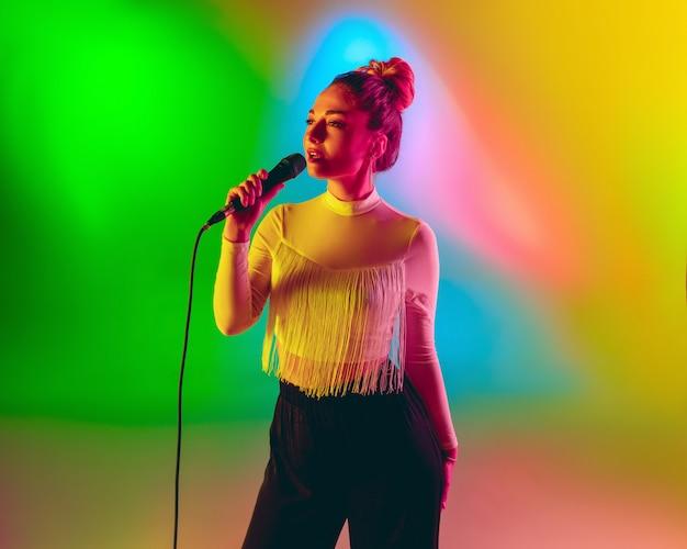 Het jonge kaukasische musicus spelen, die op gradiëntruimte zingen in neonlicht. concept van muziek, hobby, festival Gratis Foto