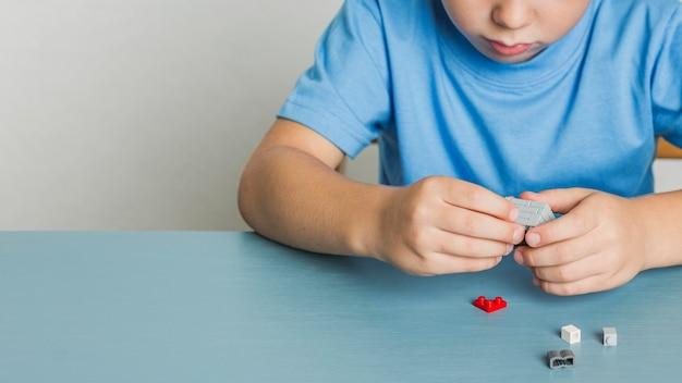 Het jonge kind van de close-up spelen met lego Gratis Foto