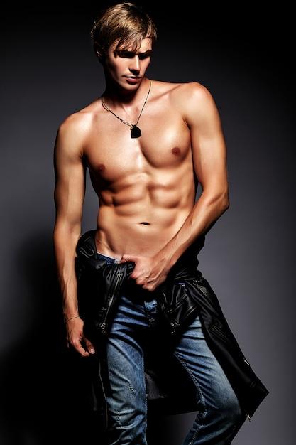 Het jonge knappe gespierde geschikte mannelijke modelmens stellen in studio die zijn buikspieren in leerjasje toont Gratis Foto