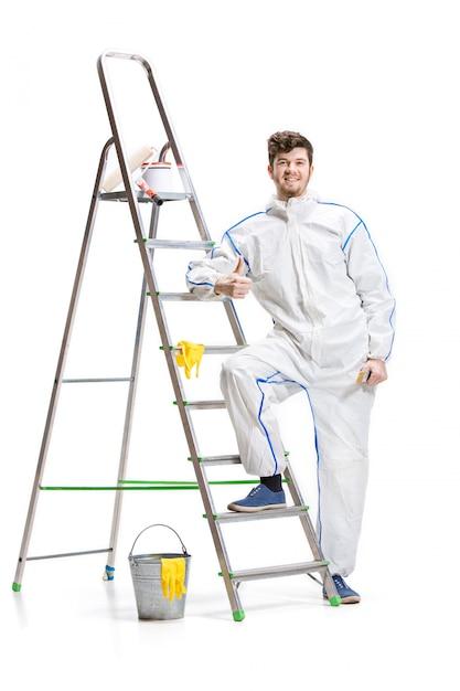 Het jonge mannelijke decorateur schilderen met een verfrol en een ladder die op witte muur wordt geïsoleerd. Gratis Foto