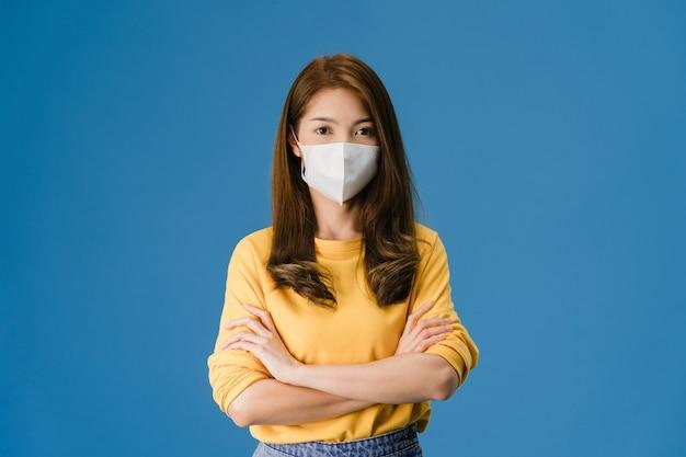 Het jonge meisje dat van azië medisch gezichtsmasker met gekruiste wapens draagt, kleedde zich in casual doek en kijkt naar camera die op blauwe achtergrond wordt geïsoleerd. zelfisolatie, sociale afstand nemen, quarantaine voor coronavirus. Gratis Foto