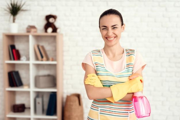 Het jonge meisje maakt het huis met detergentia schoon. Premium Foto