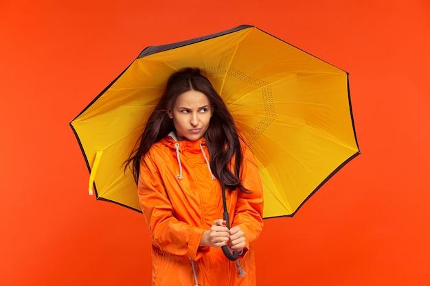 Het jonge meisje poseren in studio in herfst jas geïsoleerd op rood. menselijke negatieve emoties. concept van het koude weer. vrouwelijke mode-concepten Gratis Foto