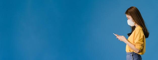 Het jonge meisje van azië draagt medisch gezichtsmasker gebruik mobiele telefoon met gekleed in casual doek. zelfisolatie, sociale afstand nemen, quarantaine voor coronavirus. panoramische banner blauwe achtergrond met kopie ruimte. Gratis Foto