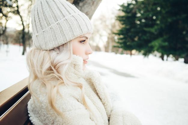 Het jonge mooie blondemeisje zit op een bank in het park in de winter Premium Foto