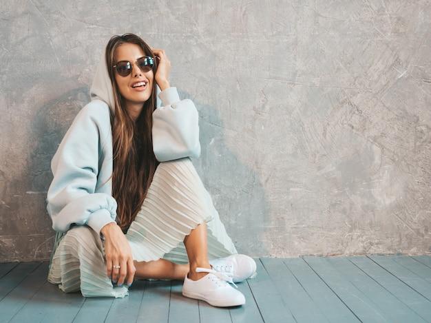 Het jonge mooie glimlachende vrouw kijken. trendy meisje in casual zomer hoodie en rok kleding. op de vloer zitten Gratis Foto