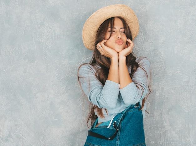 Het jonge mooie glimlachende vrouw kijken. trendy meisje in casual zomer overall kleding en hoed ... eend gezicht maken Gratis Foto