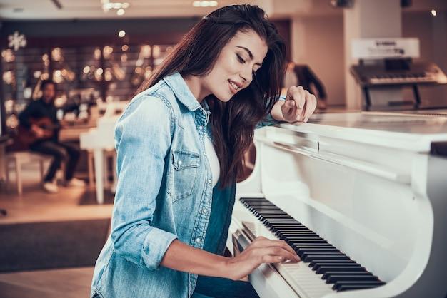 Het jonge mooie meisje speelt piano in muziekopslag. Premium Foto