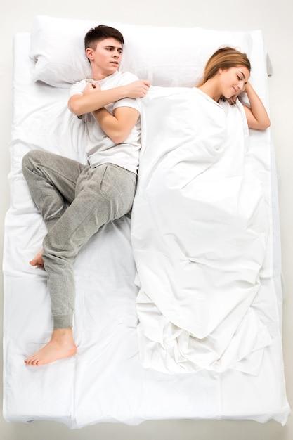 Het jonge mooie paar liggend in een wit bed, liefde lconcept, bovenaanzicht Gratis Foto