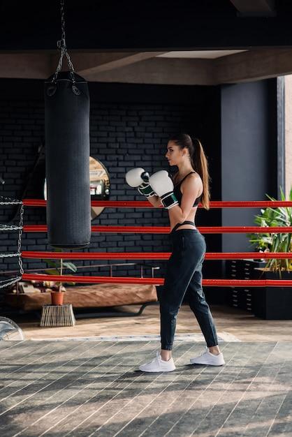 Het jonge mooie sportenmeisje in sportkleding en bokshandschoenen raakt een bokszak in moderne zwarte gymnastiek. Premium Foto