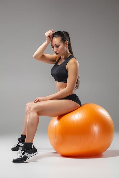 Het jonge, mooie, sportieve meisje doet oefeningen op een fitball in de sportschool op een grijze achtergrond Gratis Foto