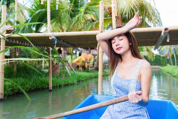 Het jonge mooie vrouw ontspannen door boot te peddelen Gratis Foto