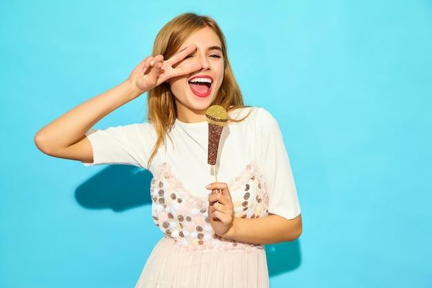 Het jonge mooie vrouw zingen met steunen valse microfoon. trendy vrouw in casual zomerkleding. grappig model dat op blauwe muur wordt geïsoleerd Gratis Foto