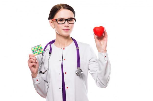 Het jonge mooie vrouwelijke hart en de pillen van de artsenholding in haar handen op witte achtergrond Premium Foto