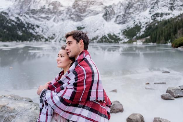 Het jonge paar bedekt met heldere deken staat voor bevroren hooglandmeer Gratis Foto