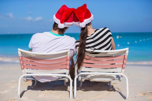 Het jonge paar in kerstmanhoeden geniet van strandvakantie Premium Foto