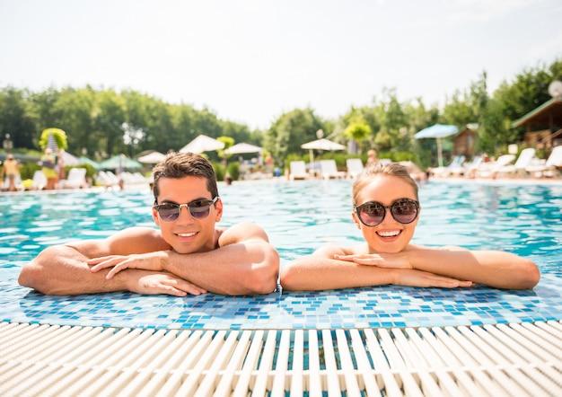 Het jonge paar ontspannen in toevlucht zwembad. Premium Foto