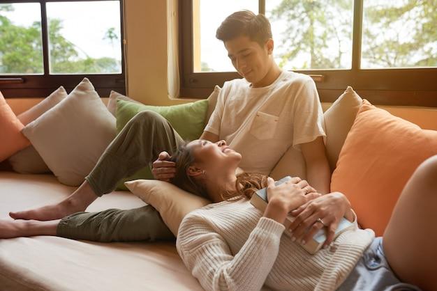 Het jonge paar ontspannen op de bank die thuis van een boek en een bedrijf van elkaar geniet Gratis Foto