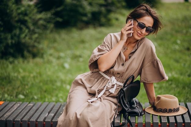 Het jonge park van de vrouwenzitting die telefoon met behulp van Gratis Foto