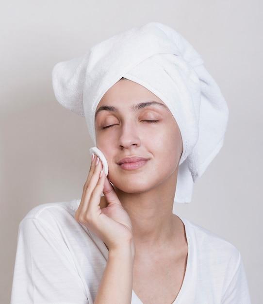 Het jonge proces van het vrouwen schoonmakende gezicht Gratis Foto