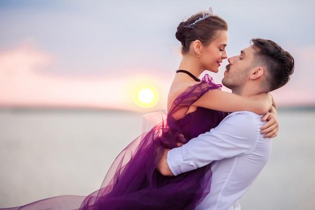 Het jonge romantische paar ontspannen op het strand die op de zonsondergang letten Gratis Foto