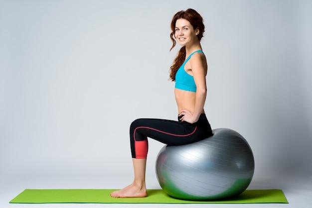 Het jonge roodharige meisje zit op gymnastiekbal. Premium Foto