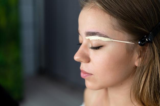 Het jonge schoonheidsspecialist kaukasische meisje houdt modelwenkbrauwcorrectie Premium Foto