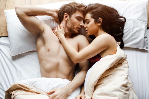 Het jonge sexy paar heeft intimiteit op bed. heel dicht bij elkaar liggen. vrouwelijk model omarmen man. liegen met gesloten ogen. seks in bed. witte kussens. slapen. Premium Foto
