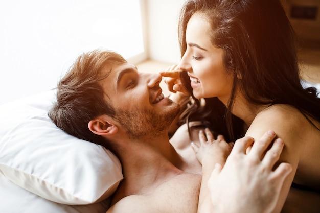 Het jonge sexy paar heeft intimiteit op bed. vrolijke leuke positieve gelukkige mensen glimlachen naar elkaar. ze lag op hem. gelukkige paar samen. daglicht. Premium Foto